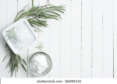 cosmetic cream and bath salts with lavender leaves on white wood surface