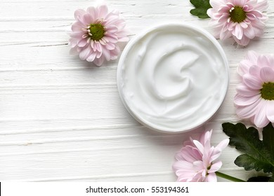 Cosmetic cream container and pink flowers on white wooden background from top view