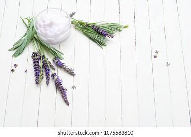 cosmetic cream and fresh lavender flowers on white wooden table background
