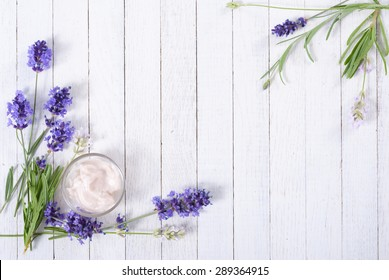 cosmetic cream and lavender flowers on white wood table background