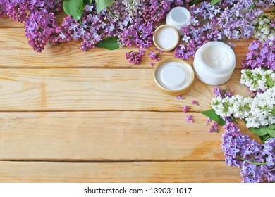 cosmetic cream, lily and lilac flowers bunch on wooden background