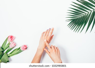 Cosmetic cream on female hands, palm branch and bouquet of pink tulips on white table top view