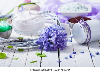 cosmetic cream product samples with hyacinth flowers on white wooden background