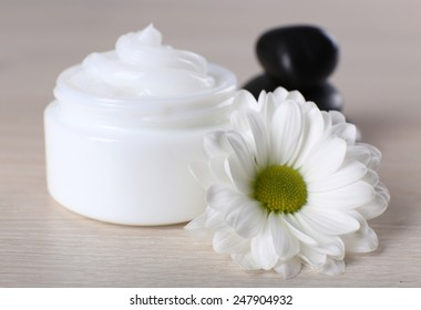 Cosmetic cream with spa stones and chamomile on wooden background