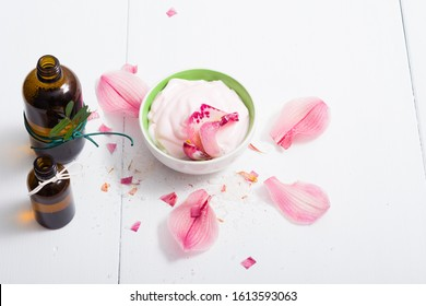 cosmetic cream, tincture, essential oil bottles, with pink flower petals, white wood table