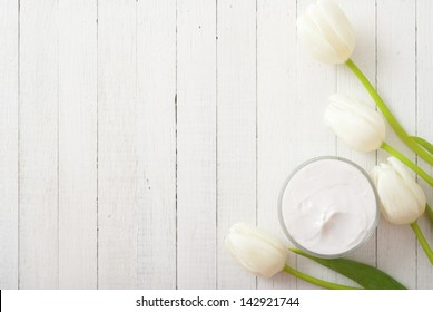 cosmetic cream with tulips on white wooden