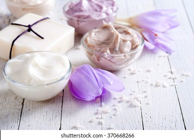 cosmetic cream variations, soap and autumn crocus herbal flower on white wooden table