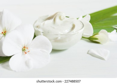 cosmetic cream with white flowers on bright wooden table