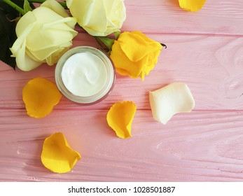cosmetic cream, yellow rose on a pink wooden