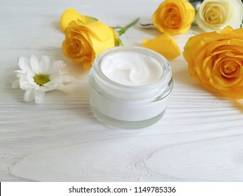 cosmetic cream, yellow rose on a white wooden background