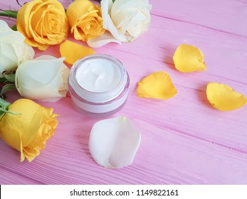 cosmetic cream, yellow rose on a pink wooden background