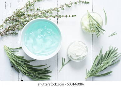 cosmetic creams with lavender and thyme leaves on white wooden table background
