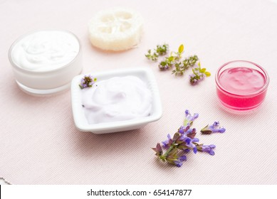 cosmetic creams, luffa sponge and herbal flowers on pink cloth background