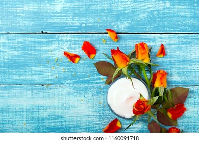 cosmetic creams and rose flowers on blue wooden table background