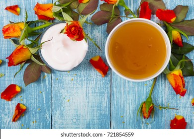 cosmetic creams and rose flowers on old blue wood table background