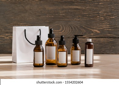 Cosmetic dark amber glass bottles on wooden background. Closeup, copyspace. Beauty blogging, salon treatment concept, brand packaging mockup
