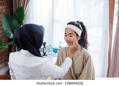 Cosmetic doctor examining female client in office. Doctor checking woman's face, beautician hands touching woman face