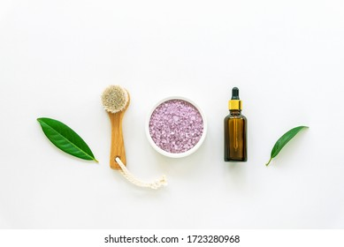 Cosmetic face brush, lavender scrub and skin serum in a bottle on white background. Natural cosmetics concept, zero waste. Top view, falt lay.