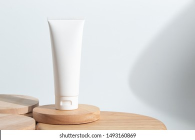 cosmetic fashion cream lotion liquid bottle tube product packaging and long shadow on white background wood plate dish in beauty skincare spa treatment healthcare medical concept