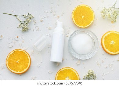 Cosmetic foam pump bottle containers with fresh orange slices, Blank label for branding mock-up, Natural Vitamin C beauty product concept.
