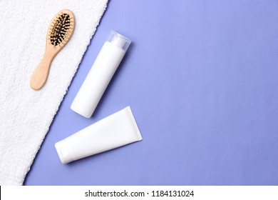cosmetic for hair care, comb and towel on a colored background top view. flatlay