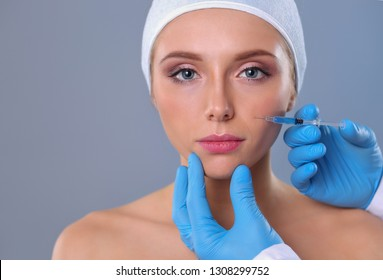 Cosmetic injection on the pretty woman face. Isolated on gray background. Cosmetic injection