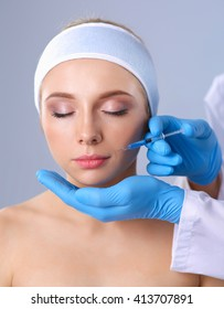 Cosmetic injection on the pretty woman face. Isolated on gray background