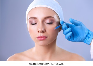Cosmetic injection the pretty woman face. Isolated on gray background