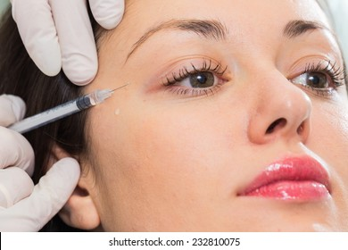 Cosmetic injection in the spa salon. Beautician makes injection into the patient's face. Beauty injections, mesotherapy, revitalization, cosmetic medicine injection - the concept of rejuvenation.