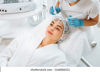 Cosmetic innovations. Nice young woman lying on the medical bed while having a microcurrent therapy procedure