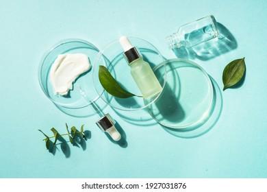 Kosmetisches Laborkonzept . Glasblattschale mit Kosmetikprodukten und Serumflaschen auf blauem Hintergrund. Flachbild.