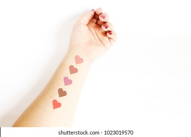 cosmetic lipstick color swatch on woman arm on white background.heart shape