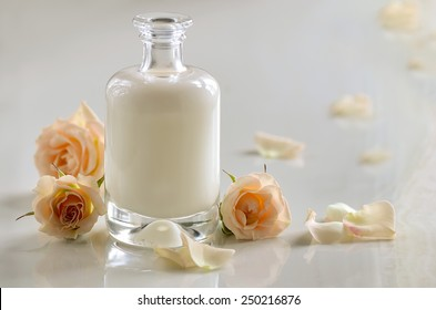 Cosmetic liquid, maybe milk, shampoo or toner, in glass bottle decorated with roses.