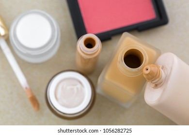 Cosmetic makeup, liquid foundation in glass bottle, plastic tube, creamy concealer, blush in pink coral shade, skin care product, selective focus