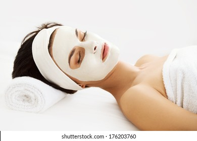 Cosmetic Mask. Beautiful Young Woman Getting a Beauty Treatment in Spa Salon. Isolated on White Backround