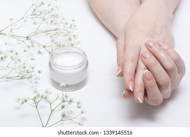 Cosmetic natural cream in a jar on a white table background.
