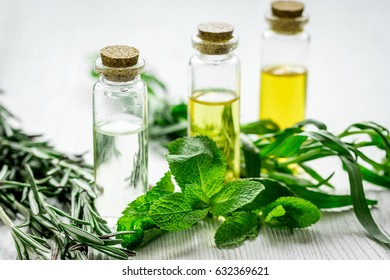 cosmetic oil in bottle with herbs on light table background