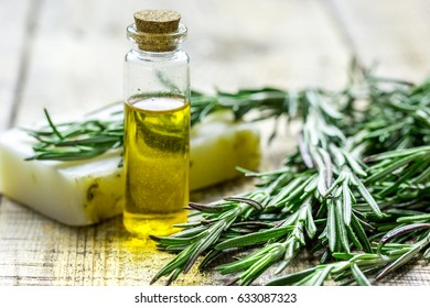 cosmetic oil in bottle and soap with herbs on light table background