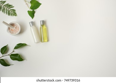 Cosmetic package containers with green leaves, pink salt,herbal . natural  organic beauty product concept mock up. Blank bottle for label own branding skincare. isolated white background.top view.