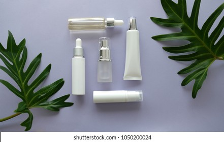 cosmetic packaging set on purple background. group of skincare cream serum oil . facial beauty cosmetic spa product. natural cosmetology concept skin treatment with green leaf and laboratory science .