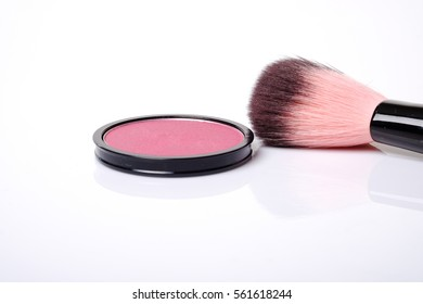 Cosmetic pink blush on and makeup brush with space for text on white background.