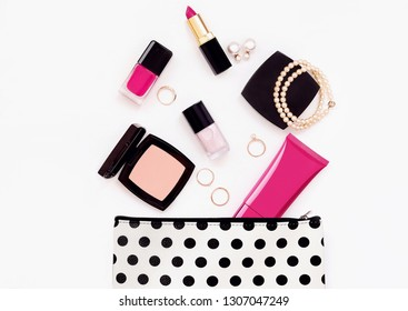 Cosmetic polka dots bag with beauty girl product and accessory. Top view