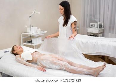 Kosmetische Packungen. Der Kosmetiker bedeckt das junge Mädchen mit Zellophan für Anti-Cellulite Hydromassage in einem modernen Kosmetologiesaal. Feuchtigkeitsspendende Körpermaske und Körperpackung.