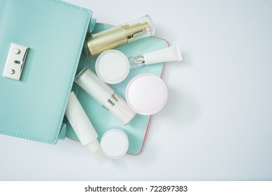 cosmetic product and woman bag isolated on white, cosmetic product