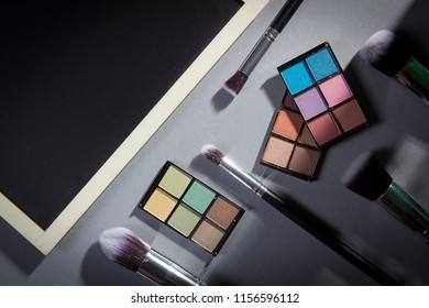 Cosmetic products and brushes for applying cosmetics on a gray background