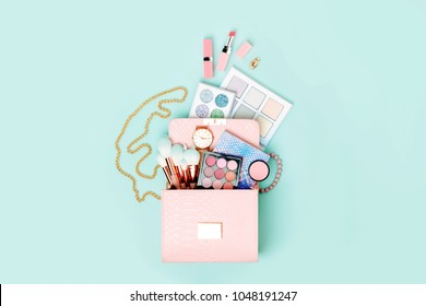 Cosmetic products flowing from Makeup bag on pastel blue background.  Flat lay, top view. Fashion concept