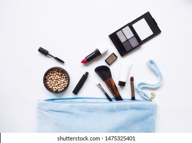 Cosmetic products flowing from Makeup bag on white background. Flat lay, top view. Fashion concept.