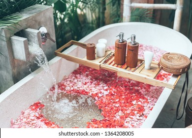 Cosmetic products on bath tub with flower petals filling with water. Organic spa relaxation in luxury Bali outdoor bathroom.