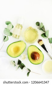 Cosmetic products on bottles with fresh avocado oil and eucalyptus aromatic leaves, white table ingredients top view. Natural skincare and beauty treatment