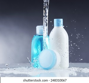 Cosmetic products in water splashes on gray background